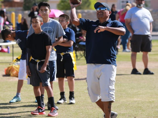 One of the El Paso Cowboys flag football team's coaches tosses passes to players during a recent practice.