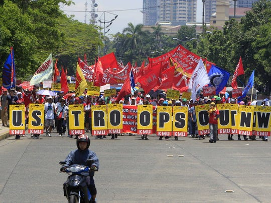 Protesters march towards the Presidential Palace after holding a rally near the US Embassy in Manila, Philippines to celebrate international Labor Day known as May Day Tuesday May 1, 2012.