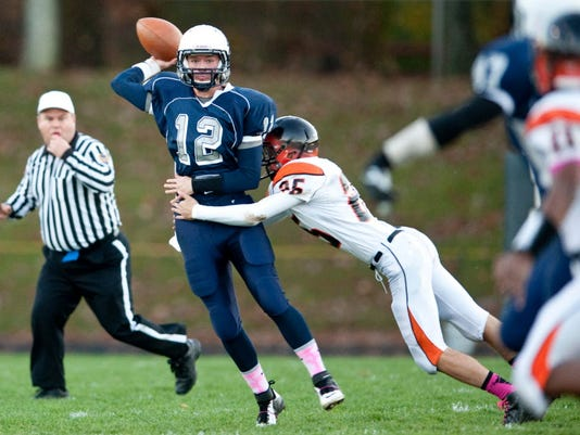 Dallastown quarterback Andrew Henry (12) is hit as he throws by Central York's Donny Crabill (25) during last season's game in Dallastown. Both Henry and Crabill are back for their teams. (GAMETIMEPA.COM -- FILE)