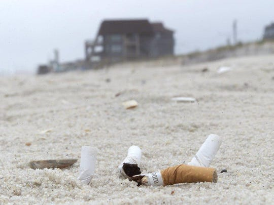 Cigarette butts litter a beach in this file photo.