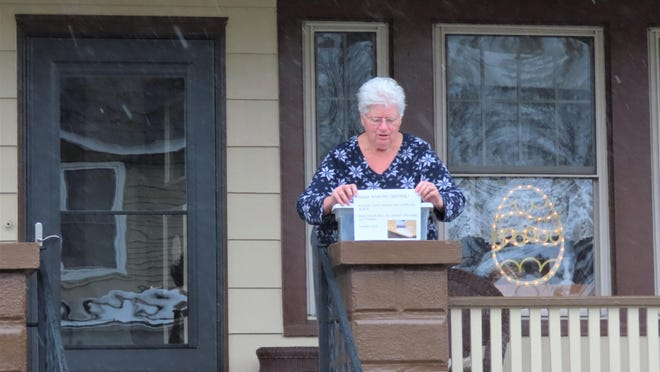Kay Lemon collects dropped-off supplies from a box on her front porch at 100 Avenue O, Matamoras, Pa.