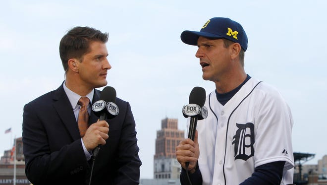 Michigan's head football coach Jim Harbaugh talks with Fox Sports Detroit's Johnny Kane before throwing   the first pitch before the Tigers game June 30. 2015,