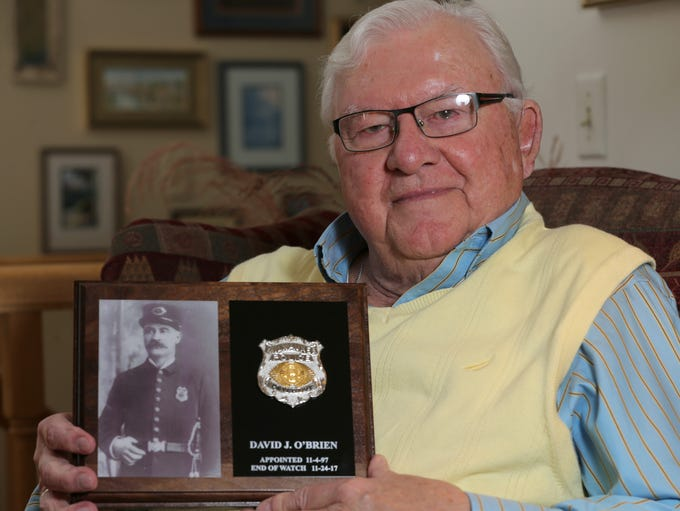 John O'Brien holds a memorial plaque for his grandfather,