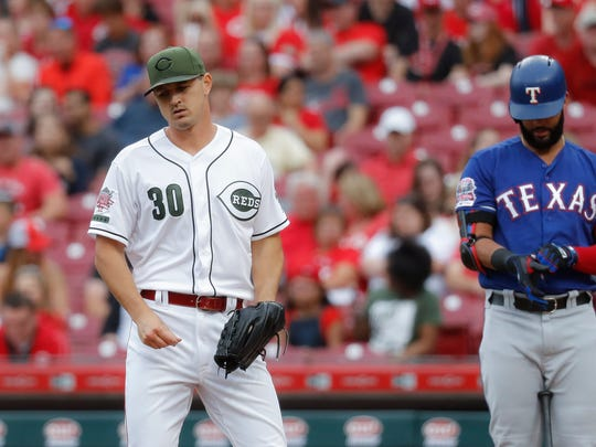 Cincinnati Reds starting pitcher Tyler Mahle (30) reacts after throwing a wild pitch in the first inning of a baseball game against the Texas Rangers, Friday, June 14, 2019, in Cincinnati. (AP Photo/John Minchillo)