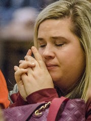 Morgan Belcher, of Livonia, is moved by a song during the vigil.