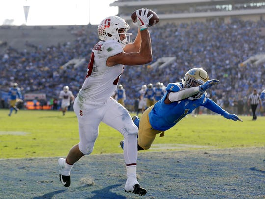 FILE - In this Nov. 24, 2018, file photo, Stanford wide receiver JJ Arcega-Whiteside, left, catches a touchdown pass next to UCLA defensive back Darnay Holmes during the second half of an NCAA college football game in Pasadena, Calif. Stanford's best offense has been having K.J. Costello throw the ball up to Arcega-Whiteside and let the physical receiver come down with the catch or draw a penalty. Arcega-Whiteside has caught 14 TD passes, tying the school record set by Pro Football Hall of Famer James Lofton in 1977. (AP Photo/Marcio Jose Sanchez, File)