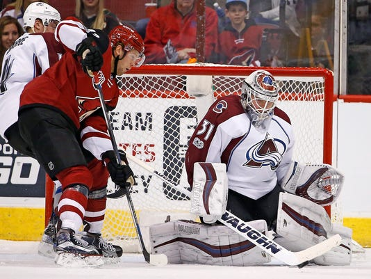 Colorado Avalanche goalie Calvin Pickard (31) makes a save on a shot as Arizona Coyotes right wing Tobias Rieder, second from left, looks for the rebound as Avalanche defenseman Tyson Barrie (4) arrives to help during the first period of an NHL hockey game, Monday, March 13, 2017, in Glendale, Ariz. (AP Photo/Ross D. Franklin)