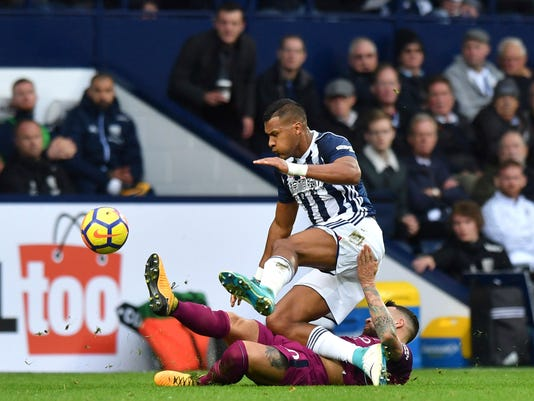 West Bromwich Albion's Salomon Rondon, and Manchester City's Nicolas Otamend, on the ground, battle for the ball during the English Premier League soccer match between West Bromwich Albion and Manchester City,  at The Hawthorns, in West Bromwich, England, Saturday Oct. 28, 2017. (Anthony Devlin/PA via AP)