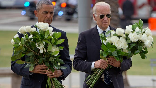 President Barack Obama with Vice President Joe Biden carry bouquets comprised of a total of 49 white roses, one in honor of each of the Pulse nightclub shooting victims, as they visit a memorial to them June 16, 2016, in Orlando, Fla.