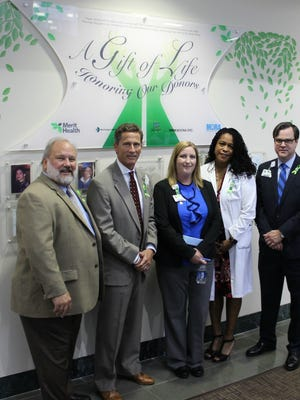 Left to right: MORA CEO Kevin Stump, Mississippi Lions Eye Bank Executive Director Mike Flynt, Merit Health Chief of Nursing Laura Knight, Hursie Davis-Sullivan, MD, Chief of Staff Merit Health Central and Jon-Paul Croom, CEO of Merit Health Central stand in front of the Gift of Life Donor Wall unveiled at Merit Health Central in Jackson on May 18.