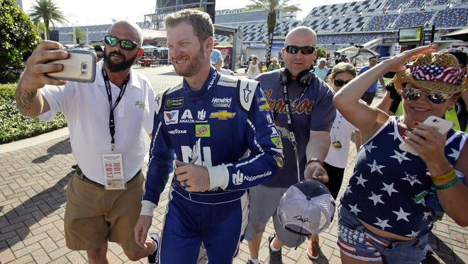 A race fan takes a selfie photo with Dale Earnhardt Jr. as others try to get autographs as he walks through the Fan Zone section after a NASCAR cup practice at Daytona International Speedway.