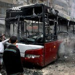 Syrians inspecti a burned bus after a missile fired by Syrian government aircraft hit the vehicle in the rebel-held neighborhood of al-Bab in Aleppo on Tuesday.