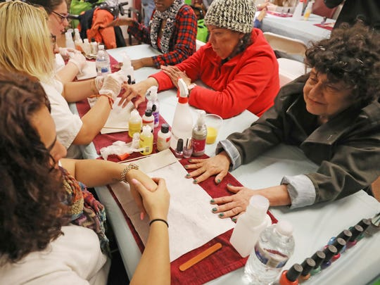 Volunteers paint the nails of some of those who came to the shelter.