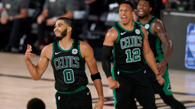 Boston Celtics' Jayson Tatum (0) celebrates after sinking a 3-point basket as Grant Williams (12) and Marcus Smart, rear, cheer him on in the second half of an NBA conference semifinal playoff basketball game against the Toronto Raptors on Tuesday, Sept. 1, 2020, in Lake Buena Vista, Fla.