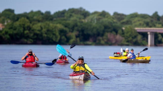 Members of the Friends of the Kaw smile as they make their way toward the boat ramp by the Topeka weir Wednesday morning. The group made a stop in Topeka as its halfway point on the 173-mile journey.