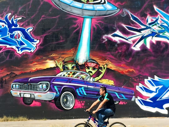 A bicyclist takes an out-of-this-world ride Wednesday by a mural at Third Avenue and Coles Street.