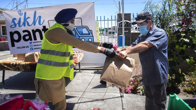 Parkpirt Nijjar, left, hands a bag of food to Ramiro Morales at the Sikh Pantry's drive-up grocery giveaway held at the The Stockton Gurdwara Sahib in south Stockton on May 3.