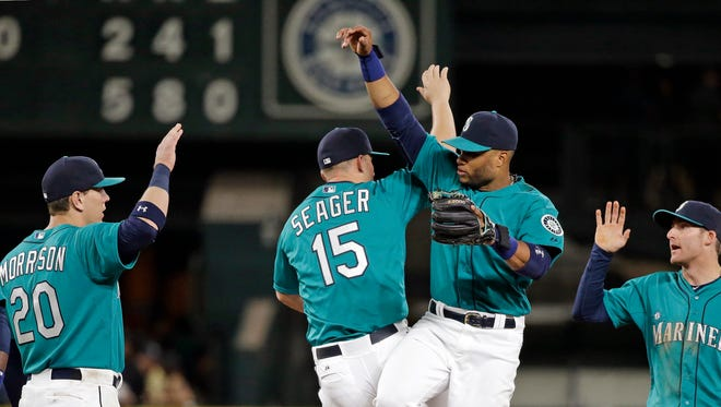 Seattle Mariners' Logan Morrison (20), Kyle Seager (15), Robinson Cano and Brad Miller share congratulations after the team defeated the Houston Astros in a baseball game Friday, June 19, 2015, in Seattle. The Mariners won 5-2.