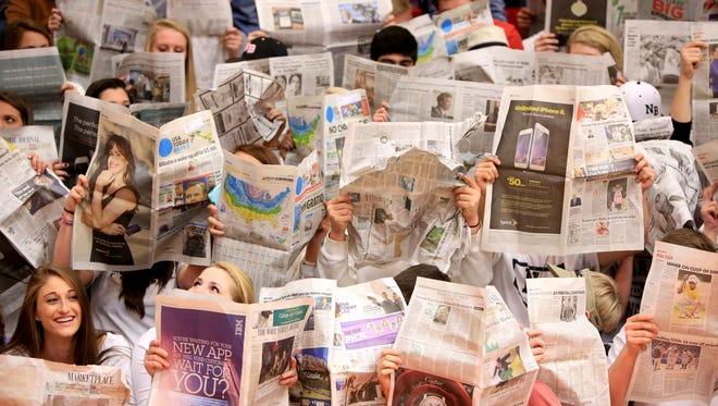 North Buncombe's student section holds up newspaper during starting introductions for the Feb. 6 game between the Black Hawks and Warriors.