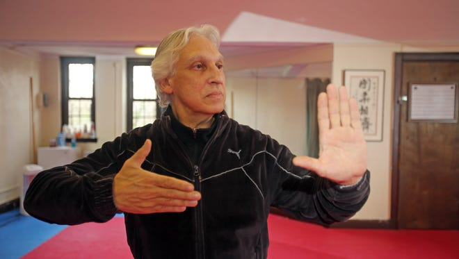 Domingo Colon demonstrates the second stage of a Tai Chi move at his school in Bronxville. The workout builds strength, balance and flexibility and is suitable for people of all ages.