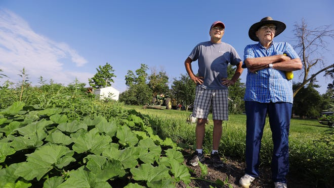 Don Wimmer,  right, looks over fields of vegetables with his son, Denny, on their farm in Arispe on Aug. 1, 2014.  Don was born on the farm in 1926 and worked conventional crops and livestock there until his retirement.  Denny left his sales career in Chicago to return and launch an organic operation on the family's 76 acres of land.