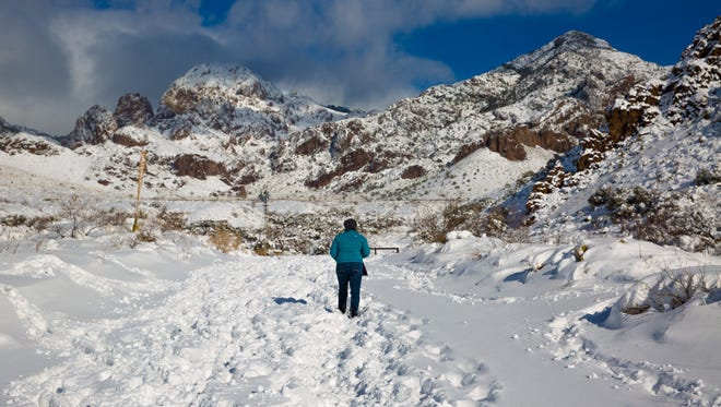 A woman walks though a snow-covered Soledad Canyon on Sunday afternoon.
