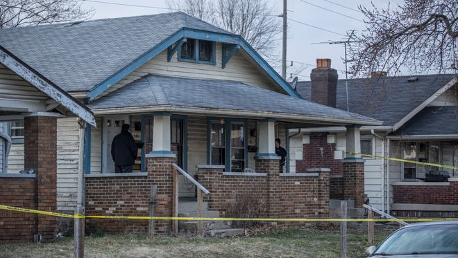 An IMPD officer and a detective stand on the porch of a home in the 700 block of North Grant Avenue where a man was shot and killed Friday.