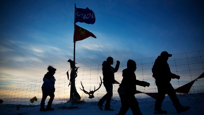 A Native American tribal flag stands atop a hill overlooking the Oceti Sakowin camp where people have gathered to protest the Dakota Access oil pipeline in Cannon Ball, N.D., Saturday, Dec. 3, 2016.
