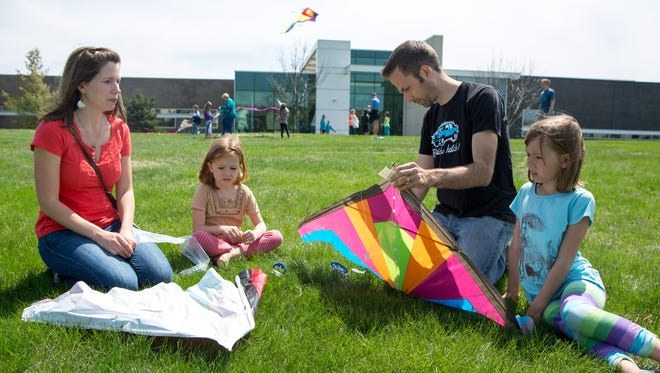 Lydia Hol, Ruby Hol, 6, Tyler Hol and Claira Hol, 8, put together kites during Kites on the Green in 2014. Johnston's annual kite festival returns this Saturday.