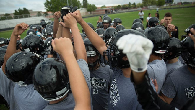 The Oñate football team takes a quick huddle between drills at Oñate High School. Tuesday Aug 1, 2017.