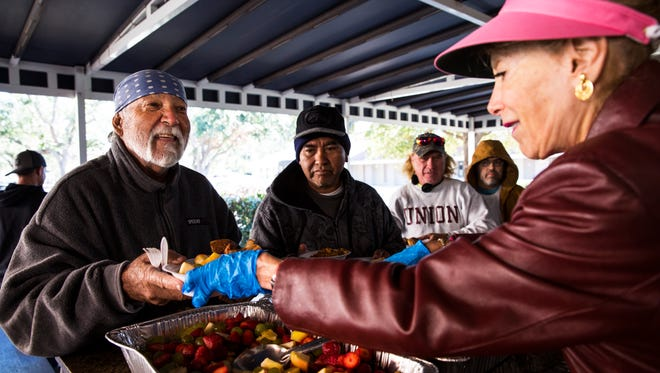Rene Lira, left, thanks volunteer Jackie Sallade during lunch at Justin's Place Feeding Ministry in East Naples on Thursday, Jan. 4, 2018. Besides serving their daily hot meals, St. Matthew's House has received blanket donations and has put out another request for adult winter jackets to help the homeless deal with the cold weather.