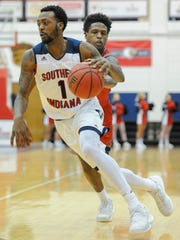 Southern Indiana guard Jeril Taylor (1) drives past William Jewell guard Clark Minnifield (3) during a Jan. 5 game at the USI Physical Activities Center.