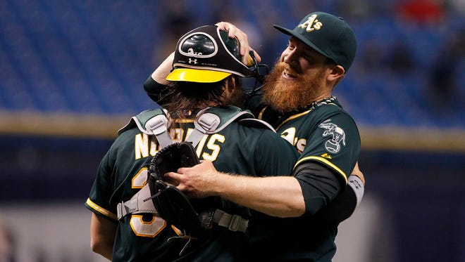 Oakland Athletics relief pitcher Sean Doolittle (62) and catcher Derek Norris (36) hug and congratulate each other after they beat the Tampa Bay Rays at Tropicana Field. Oakland Athletics defeated the Tampa Bay Rays 3-2.