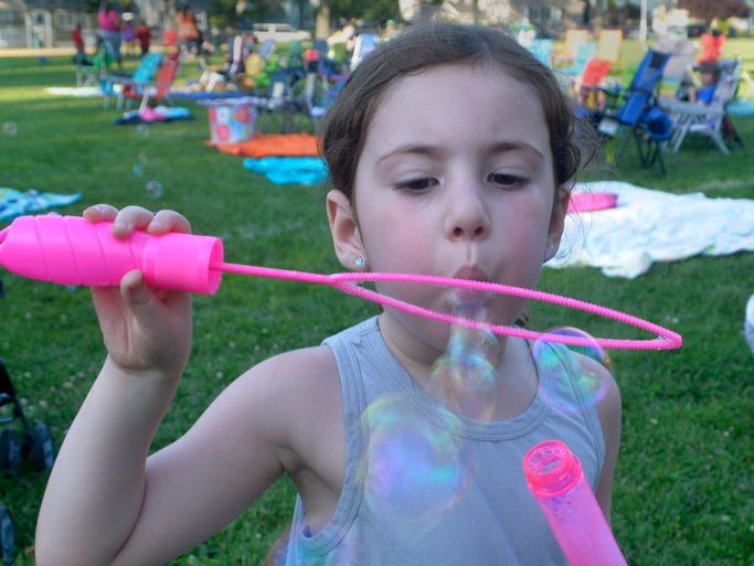 Five-year-old Jordanna Silverstein of Fanwood passes the time in Fanwood's LaGrande Park during Tuesday night's Party in the Park. Several hundred people attended the opening night for the borough's summer outdoor movie series.