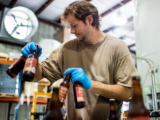 Jeremy Conner boxes bottles of Ragin' Cajuns beer at