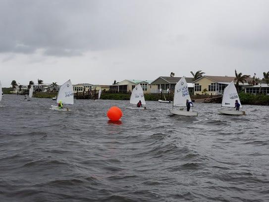 Twenty-two Optimist dinghies in two fleets, sailing