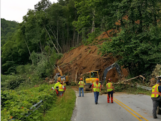 A DOT crew works to remove debris shortly after a mudslide