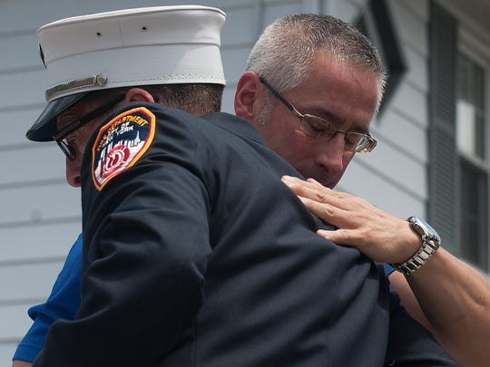 Audubon resident, Lou Giaccardo, who was working on the 87th floor of the North Tower, facing, and a retired FDNY firefighter, Lt. William Bach from Ladder 119 Brooklyn, NY, embrace during the Audubon's Fire Department unveiling of its 9/11 memorial featuring a piece of the World Trade Center.