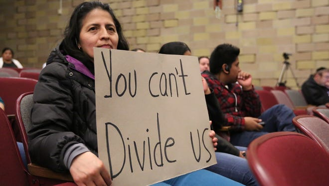 Nieves Pinos from Spring Valley holds a sign during the Dec. 15 school board meeting at East Ramapo High School.
