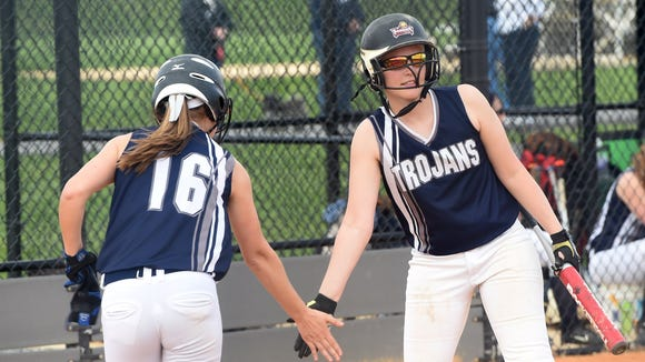 Chambersburg's Caeley Etter, left, is congratulated by teammate Tara Harmon after scoring a run against Shippensburg last year. This season, the Trojans boast a strong team chemistry.