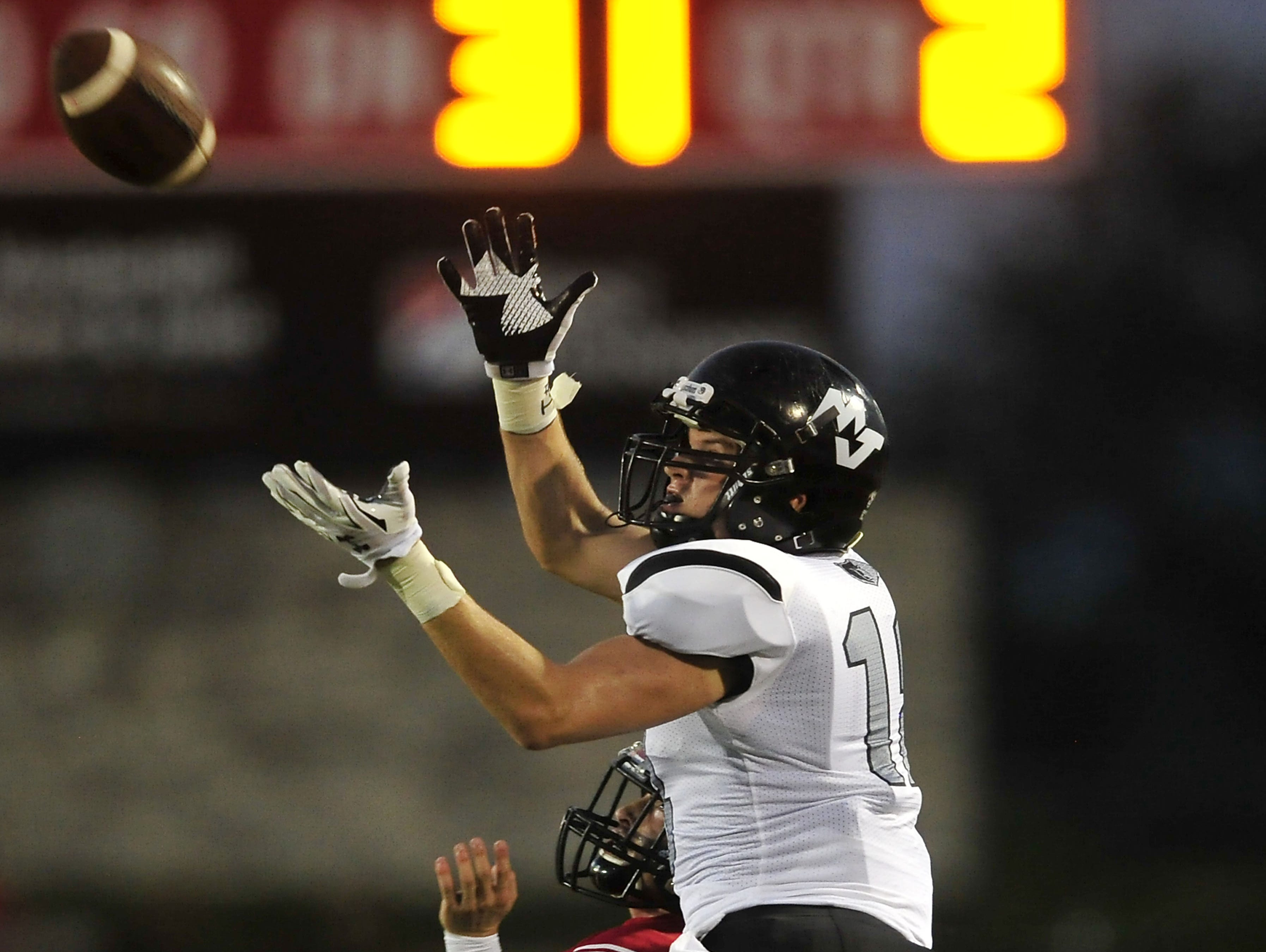 Mt. Juliet's Trey Pruitt (18) catches a pass over Ravenwood's Zack Stallcup during the first half at Ravenwood High School in Brentwood, Tenn., Friday, Sept. 4, 2015.