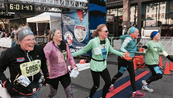 Gladys Racette, left, of Fillmore, Calif., finishes her first marathon Sunday in what became a reunion of school chums, holding hands with pals from the 1980 and '81 classes at Detroit's defunct Dominican High School. Racette, 53, said she lost 100 pounds since taking up running in 2013.