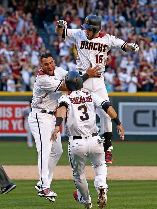Arizona Diamondbacks' Chris Owings (16) celebrates his walk-off single against the San Francisco Giants with David Peralta, left, and Daniel Descalso (3) in an opening day baseball game Sunday, April 2, 2017, in Phoenix. The Diamondbacks defeated the Giants 6-5. (AP Photo/Ross D. Franklin)