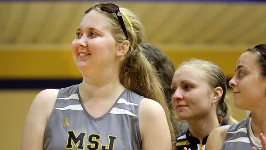 Lauren Hill, a freshman on the Mount St. Joseph women's basketball team, reacts to the applause as she is honored following the team's opening home game.