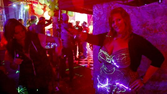 Joelle Webber gets help in demonstrating her Lazer Glo dress at Trilogy Nightclub in Philadelphia.
