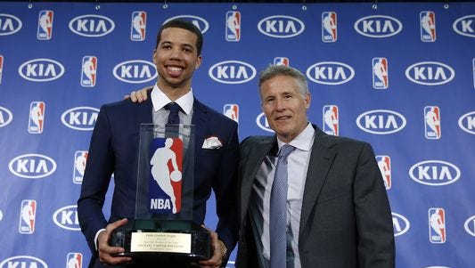 Philadelphia 76ers' Michael Carter-Williams, right, and head coach Brett Brown pose with the NBA Rookie of the Year award which was presented to Carter-Williams during a news conference at the team's practice facility, Monday, May 5, 2014, in Philadelphia.