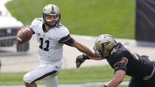 Gold quarterback David Blough is chased by Evan Panfil during the Gold & Black spring football game Saturday, April 18, 2015, at Ross-Ade Stadium on the campus of Purdue University. The Black team defeated the Gold 28-23.
