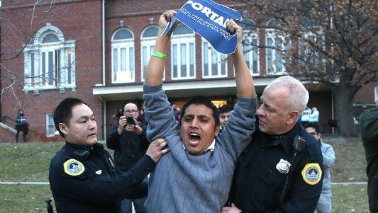 Self-identified undocumented immigrant Marco Malagon of Dallas is escorted off the grounds of Hoyt-Sherman Place after a disruption during the Iowa Freedom Summit in January. Malagon and Cesar Vargas were later convicted of trespassing.