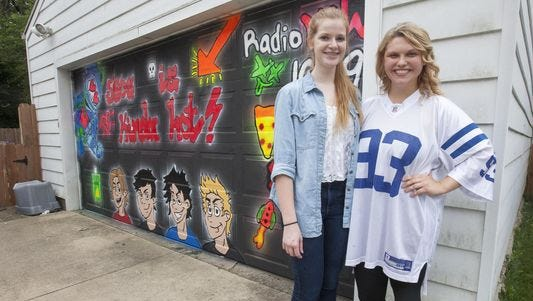Hannah Brewer, left, and Morgan Whitmer, right, stand in front of the garage door they painted in order to win a radio contest by 100.9 for free concert tickets. An anonymous letter was left for the girls condemning the artwork.