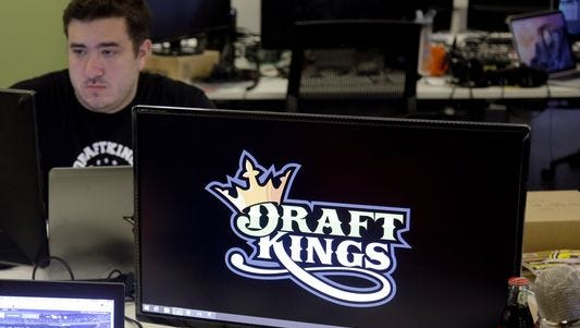 Len Don Diego, marketing manager for content at DraftKings, a daily fantasy sports company, works at his station at the company's offices in Boston in 2015. DraftKings, FanDuel and Yahoo are returning to Delaware to offer daily fantasy sports after a new state law.